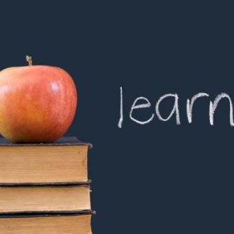 """learn"" written on blackboard with apple and books"